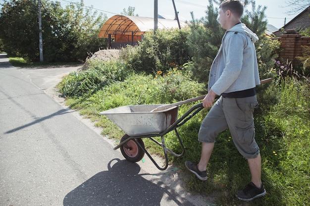 30세의 백인 남성이 여름 별장에서 길을 콘크리트로 채우기 위해 모래를 싣기 위해 정원 수레를 싣고 있습니다.