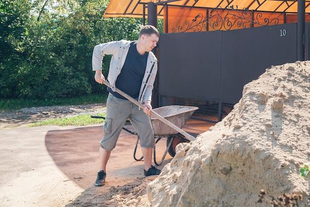 30세의 백인 남성이 여름 별장에서 콘크리트로 길을 채우기 위해 정원 수레에 모래를 싣고 있습니다.