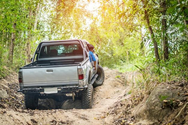 Полноприводной автомобиль преодолевает сложное бездорожье в горных лесах таиланда.