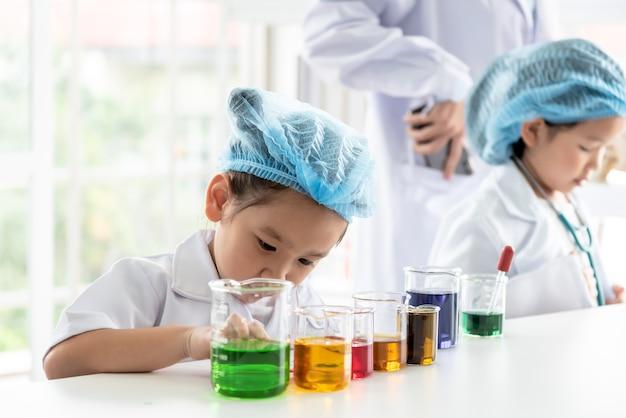 4歳のアジアの女の子、learning andは、計量カップ付きの白いテーブルで、友人の背景をぼかして、子供たちと教育の概念について科学実験を行いました。