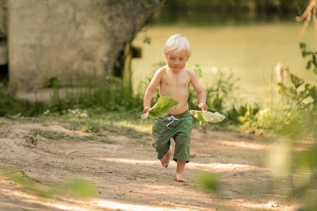 ショートパンツで裸足の4歳の男の子が川の近くの森の小道を走っています。