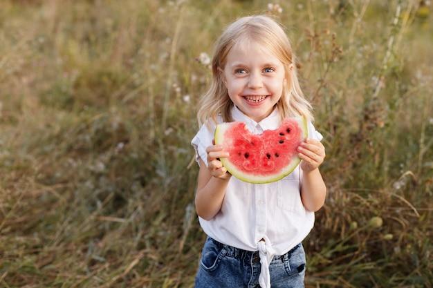 9月に5歳の女の子がスイカに微笑む。テキスト用