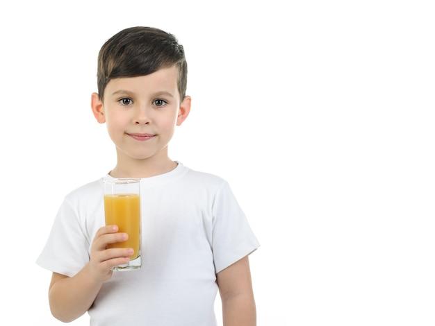 6-летний мальчик в белой футболке держит стакан с соком цитрусовых на белом фоне. изолированный фон.