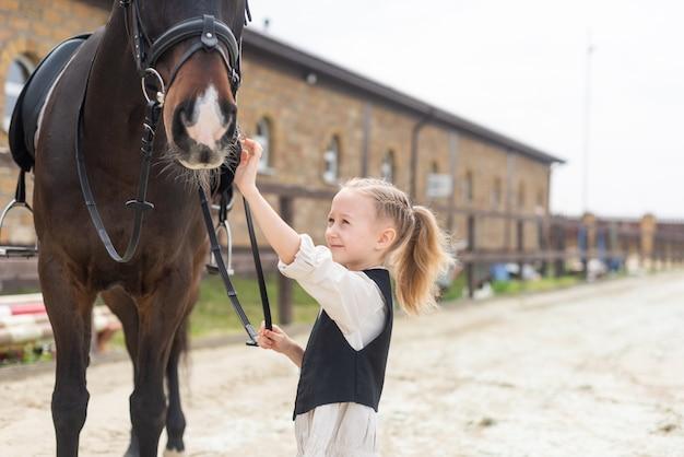 67-летняя девочка гладит лошадь и хочет покормить ее, держа лошадь за уздечку.