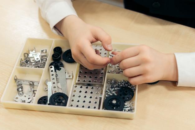 7〜8歳の男の子が、金属製の建設キットをクローズアップで遊んでいます。高品質の写真