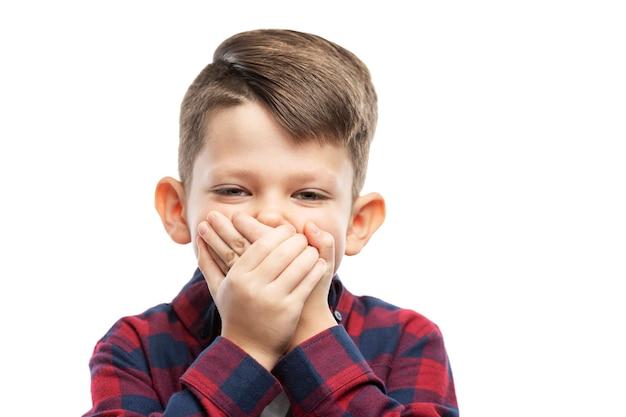 7 살 소년이 손으로 입을 가렸다. 확대. 흰 벽에 고립.