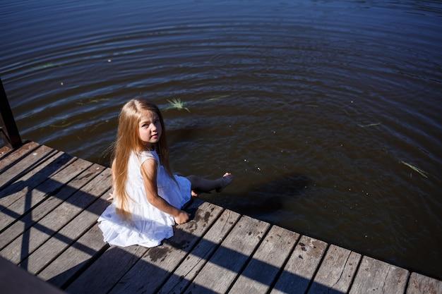 호숫가에서 긴 금발 머리를 한 7세 소녀가 물속에 다리를 놓은 채 클러치에 앉아 있습니다. 그녀는 호수에 그녀의 발을 튀긴다. 긴 머리에 하얀 드레스를 입은 맨발의 소녀.
