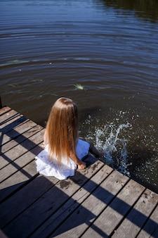 湖のほとりに長いブロンドの髪をした7歳の少女が、足を水につけてクラッチに座っています。彼女は湖に足をはねかける。長い髪の白いドレスを着た裸足の女の子。