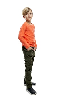 オレンジ色のセーターと緑のズボンを着た9歳の少年が、ポケットに手を入れて立っています。