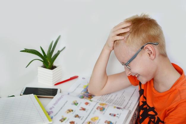不機嫌そうな顔をした9歳の少年は、遠隔教育、自宅でのオンラインレッスン、検疫中の社会的距離に従事しています。自己隔離。コンセプトオンライン教育、ホームスクーラー