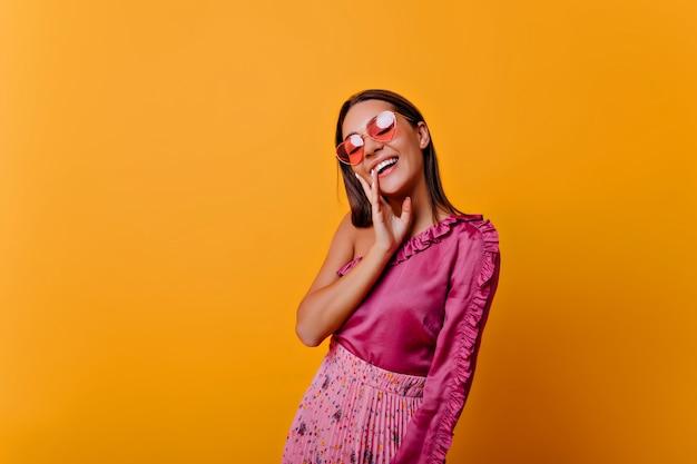 ピンクのトップスにフリルのポーズをとった、喜びを示すアルムの女性。居心地の良い雰囲気の中でヌードメイクをしたモデルの写真