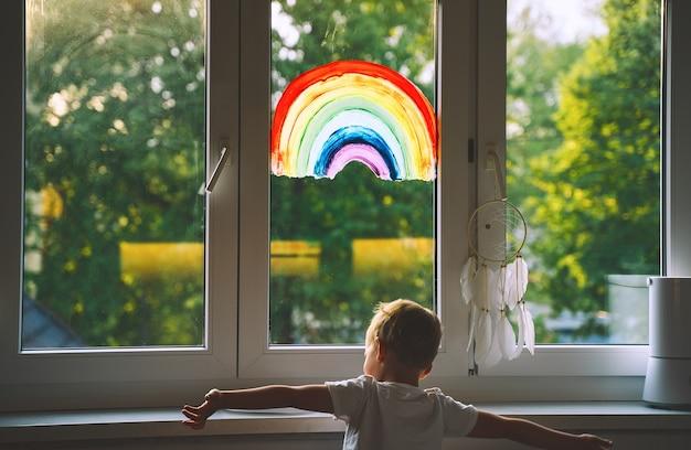 Мальчик на фоне живописи радуги на окне. фото отдыха детей дома. положительная визуальная поддержка во время карантина пандемия коронавируса covid-19 дома. семейное искусство фон