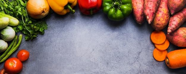 • горизонтальное натуральное питание и свежие овощи на темном фоне цементного пола, концепция чистого питания и хорошая здоровая еда для меню