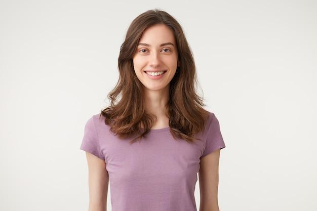 魅力的な魅力的な女性の笑顔を傷つけ、紫のtシャツを着ています