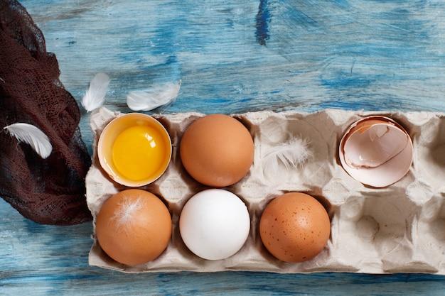 Ãâ¡青い木製の背景のボックスに卵をひねる