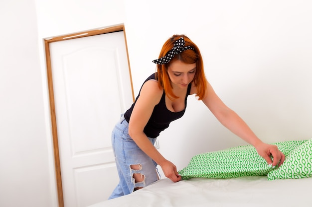 청바지를 입은 젊은 여성을 잃고 검은 티셔츠는 흰색 벽과 서랍장이있는 침실에서 흰색-녹색 기하학적 침구 침대를 청소합니다.