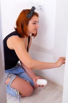 крупным планом молодая женщина в джинсах, черная футболка красит кисточку и белую краску на стенах в детской комнате с белыми стенами.