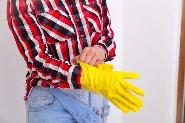 √â¡保護ゴムの黄色い手袋を着用してジーンズと格子縞のシャツの手で若い女性を失います。女性の家事と安全、ハウスキーピングのコンセプト