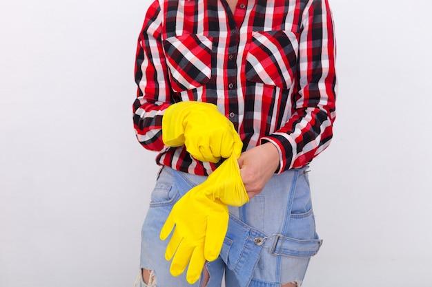 청바지와 격자 무늬 셔츠 손에 보호 고무 노란색 장갑을 끼고있는 젊은 여성의 â 최대. 여성의 가사와 안전, 가사 개념