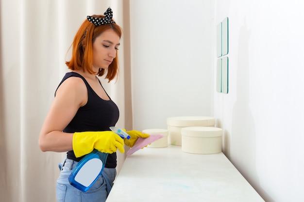 ジーンズ、黄色い手袋、格子縞のシャツを着た若い女性を失い、寝室のピンクのぼろきれと白い箪笥を拭きます。ほこりからの部屋のウェットクリーニング