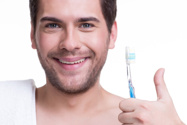 √â¡歯ブラシを持った幸せな若い男の肖像画を失う-白で隔離。