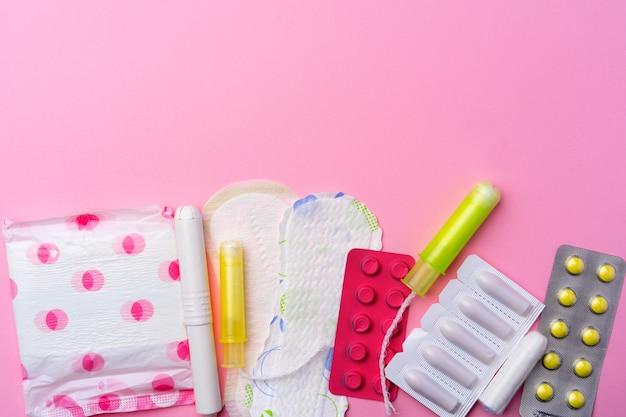 Противозачаточные таблетки, гигиенические прокладки и тампоны на розовом виде сверху