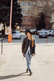 Ãâoungかわいい女の子は笑顔でポーズをとって街を歩きます