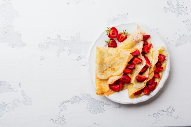 밝은 콘크리트 이전 테이블 배경에 신선한 딸기와 카라멜 ã â¡repes