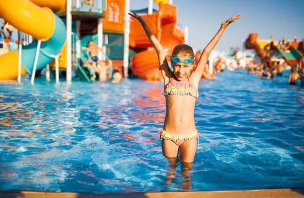 수영을 위해 파란색 안경을 쓰고 밝은 수영복을 입은 사랑스러운 소녀가 옆에 맑은 물이 있는 수영장에 서서 손을 들고 물을 튀깁니다.