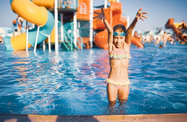 수영을 위해 파란색 안경을 쓰고 밝은 수영복을 입은 사랑스러운 소녀가 옆에 맑은 물이있는 수영장에 서서 손을 들어 올리면서 튀었습니다.