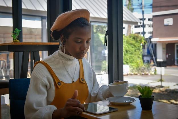 한 아프리카계 미국인 여성 사업가가 태블릿을 사용하여 커피숍에서 고객과 채팅하고 손에 커피 컵을 들고 있습니다.