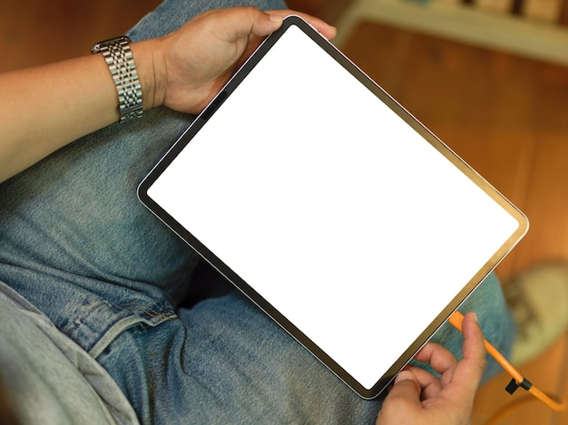 Пожилой мужчина с помощью цифрового планшета проверяет свою работу макет пустого экрана планшета