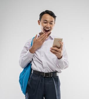 驚きの表情で携帯電話を持った中学生の制服を着たアジア人の少年と...
