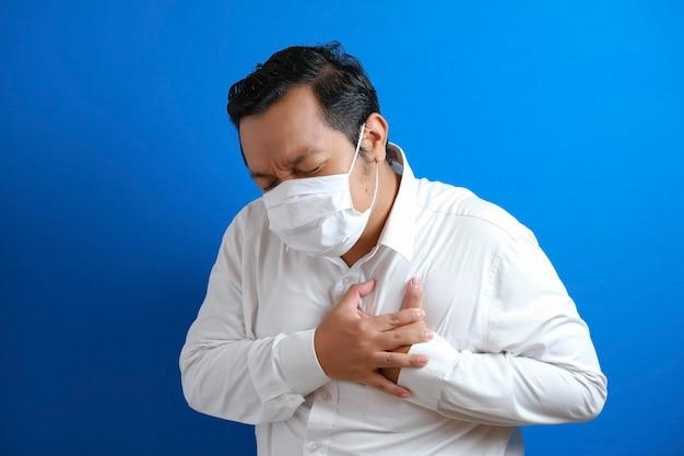 胸に痛みを感じるマスクを身に着けているアジアの太った男、左胸を保持するジェスチャー。青い背景