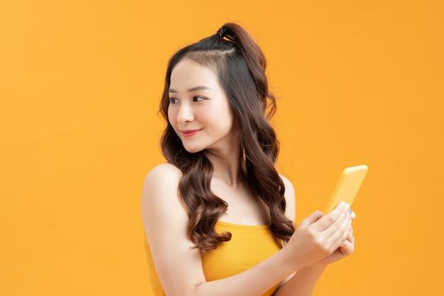 アジアの女の子が携帯電話を持って、黄色の背景を振り返ります。