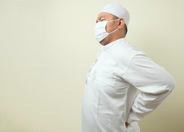 마스크를 쓴 아시아 이슬람 뚱뚱한 남자가 등에 통증을 느끼고 등을 잡고 있는 제스처