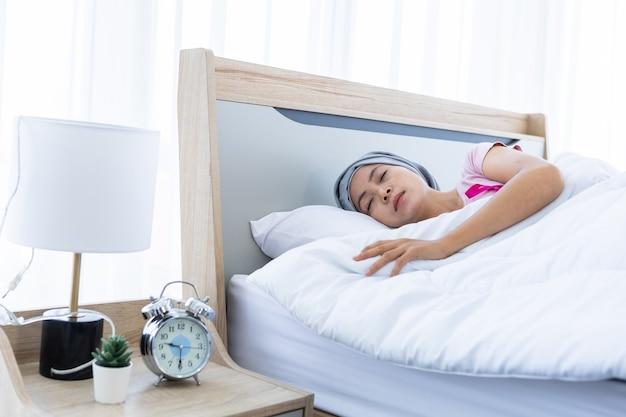 Пациент с раком молочной железы азиатской женщины с розовой лентой в платке после лечения химиотерапией, лежа на кровати с часами и лампой в спальне в доме, здравоохранение, концепция медицины