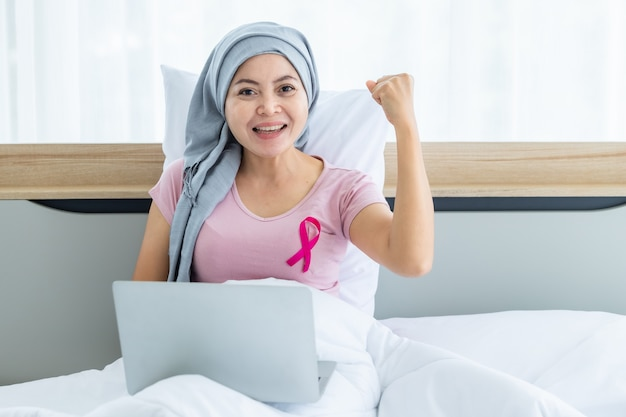 머리 스카프를 두른 분홍색 리본을 한 아시아 여성 유방암 환자 침대에 있는 노트북에서 일하는 비즈니스와 함께 화학 요법 치료를 받은 후 집, 건강 관리, 약의 침실에서
