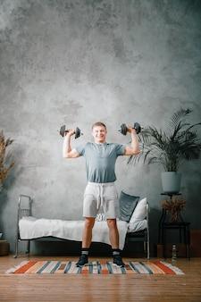 ブロンドの髪のアスリートが寝室のダンベルで上腕二頭筋を振る、オンライントレーニング。その青年は家でスポーツに出かける。