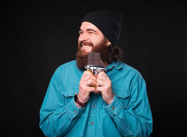 Потрясающий бородатый мужчина держит очень возбужденный шоколад с закрытыми глазами и широкой улыбкой на лице возле темной стены.