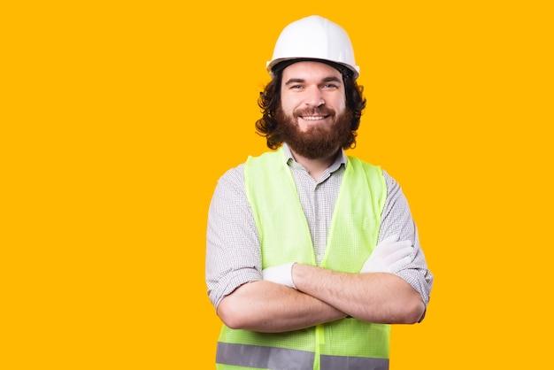 그의 팔로 카메라를보고 젊은 수염 엔지니어의 멋진 초상화는 노란색 벽 근처를 넘어