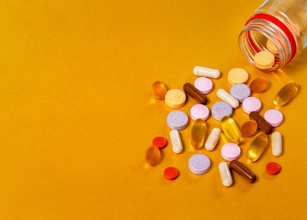 瓶からの錠剤、ビタミンa、b、c、e、d、ルテイン+ブルーベリー、ベータカラチン+海クロウメモドキ、ブラックタイムオイル、集められた、オメガ3などのさまざまなグループのビタミンのクローズアップ。