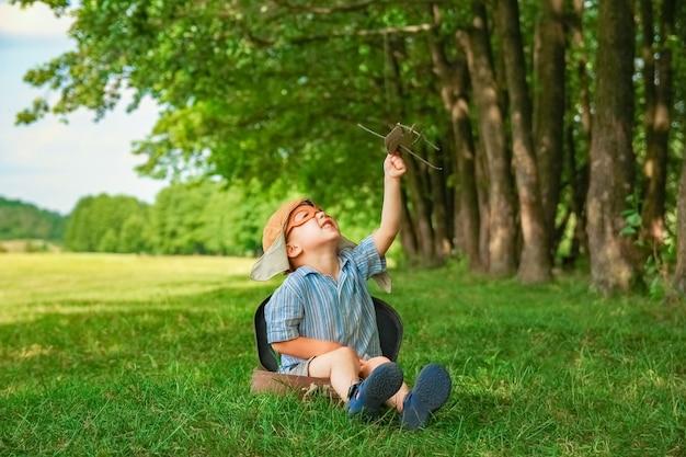 Младенец у самолета играет на природе в парке. мальчик в отпуске пилота.