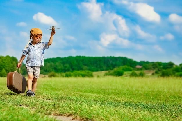 飛行機のそばの男の子が公園で自然を遊んでいます。休暇パイロットの少年。