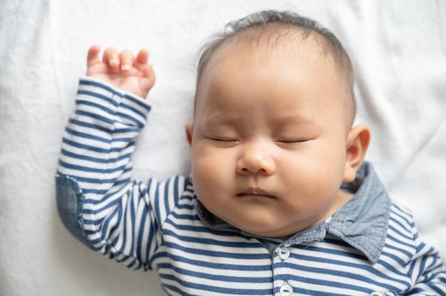 縞模様のシャツを着た男の子がベッドで寝ています。
