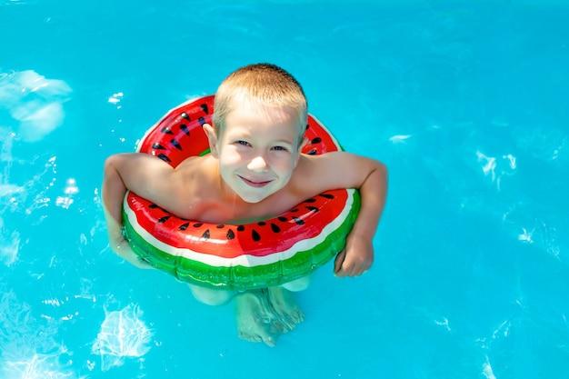 男の子は真っ赤なインフレータブルサークルの青いプールで泳ぐことを学ぶ