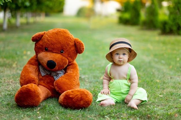 여름이면 6개월 된 남자아이가 녹색 반바지와 모자를 쓴 큰 테디베어와 함께 푸른 잔디 위에 앉아 있습니다.