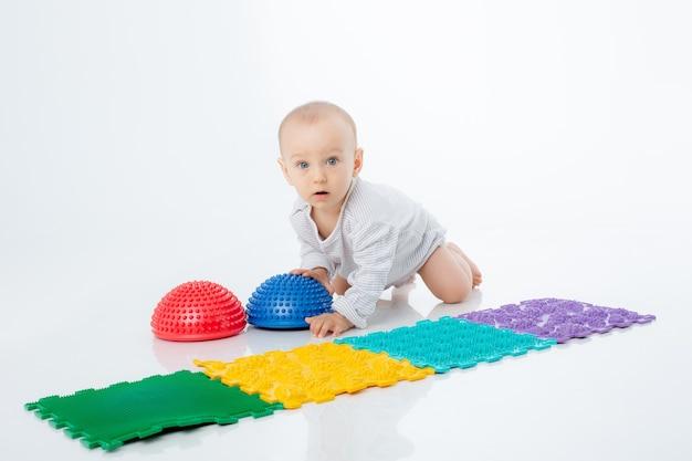 흰색 배경에 정형외과용 매트와 반구가 있는 아기가 격리되어 있습니다