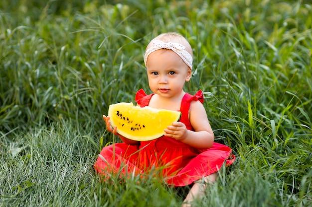 女の赤ちゃんは黄色のスイカを手に持って草に座っています。