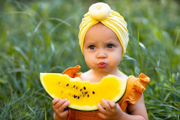 女の赤ちゃんは黄色いスイカを手に持っています。